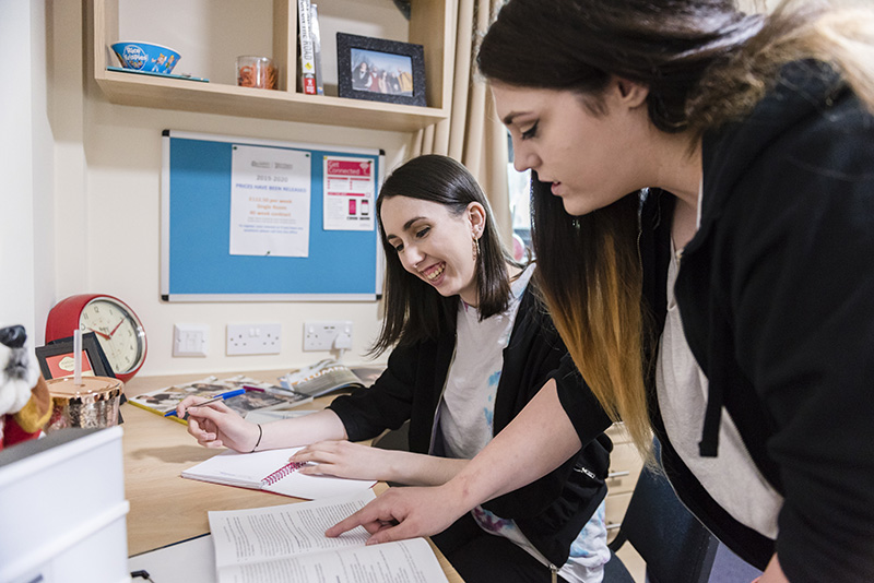 Students at a desk in Wrexham village