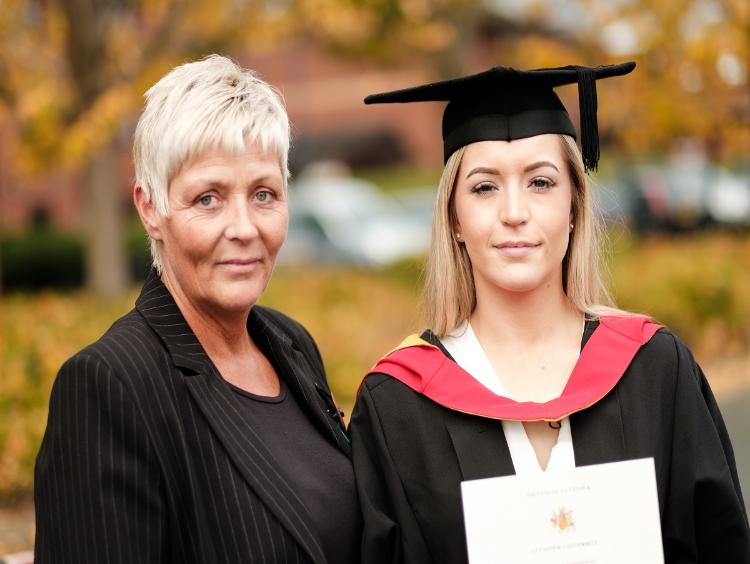 A graduate in cap and gown holding a certificate