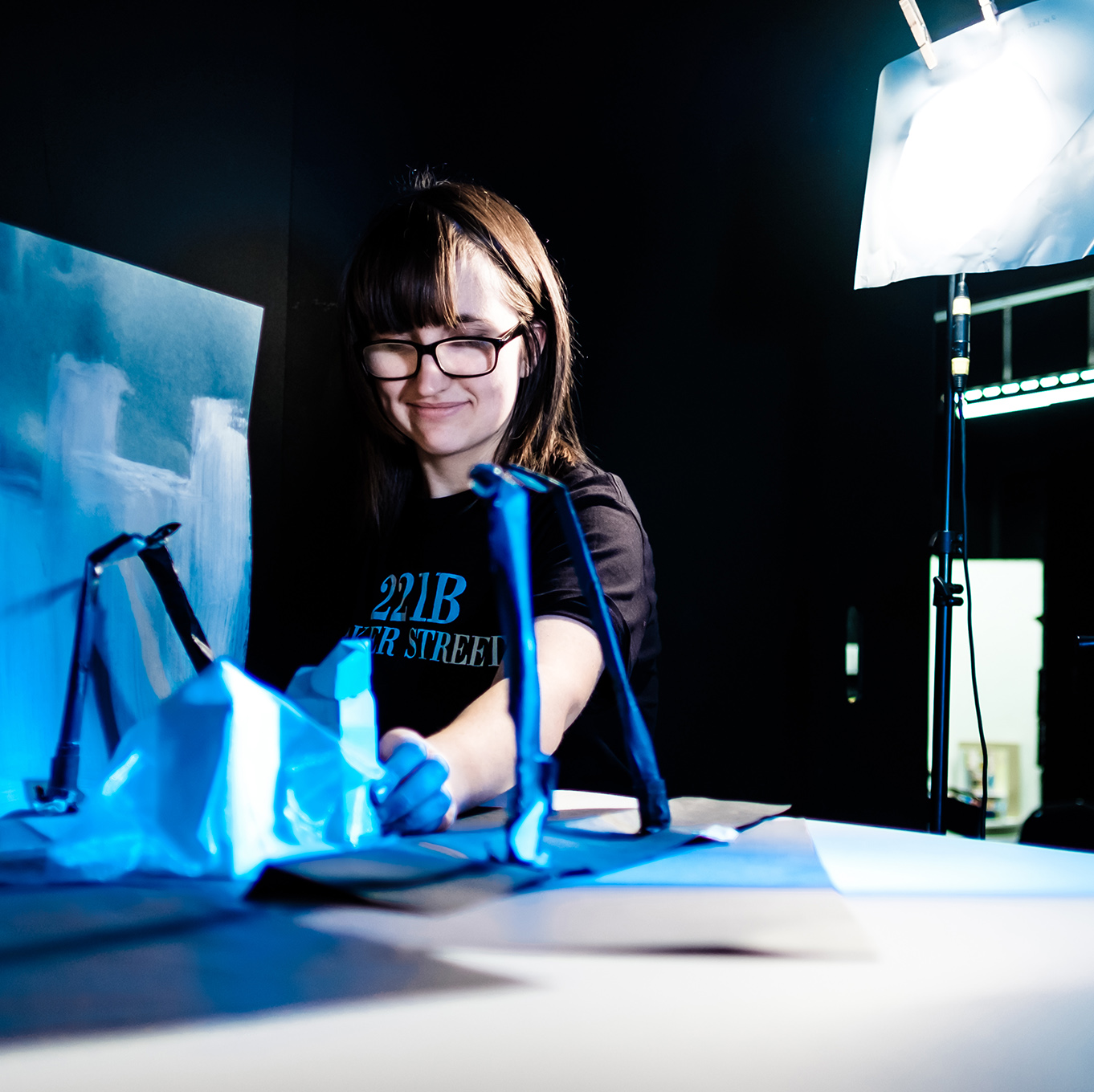 A student arranges props and models for a stop-motion animation shoot