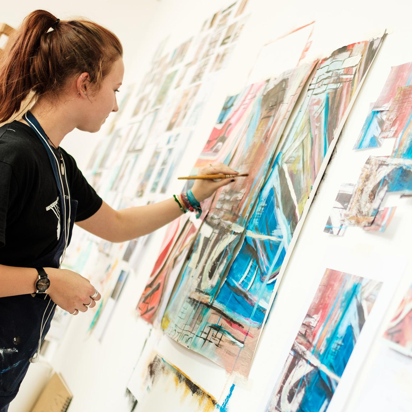 A fine art student paints the finishing touches onto her work