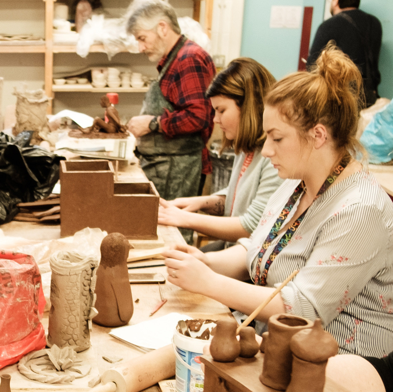 Students sitting in a workshop, hand modelling ceramics