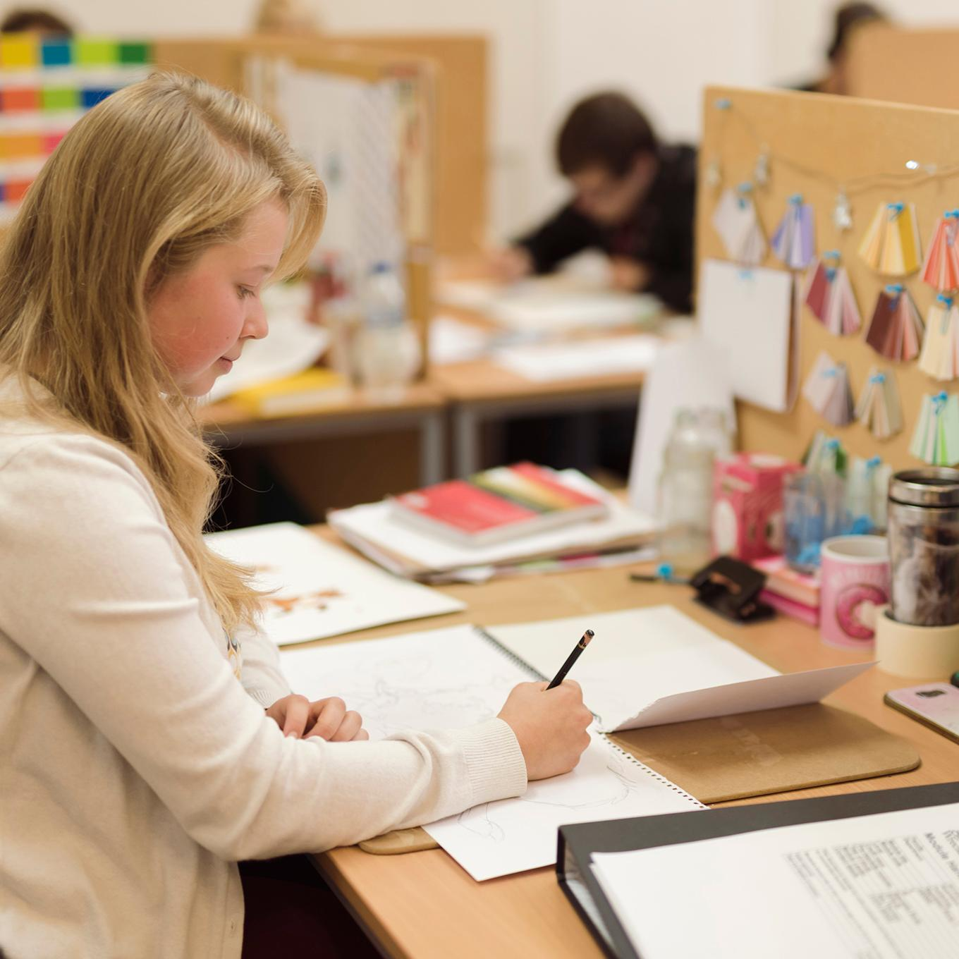 An illustration student works on a project at her workspace
