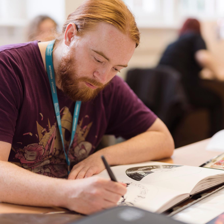 An illustration student works in his sketchbook