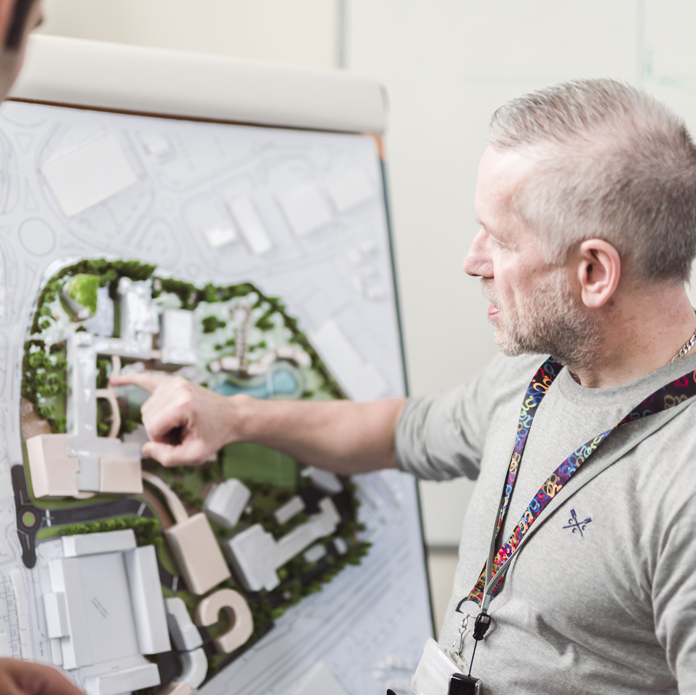 Lecturer Gareth Carr point out key features of a 3D building plan to a student