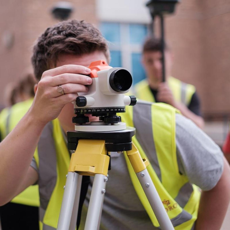 Civil engineering students using surveying equipment