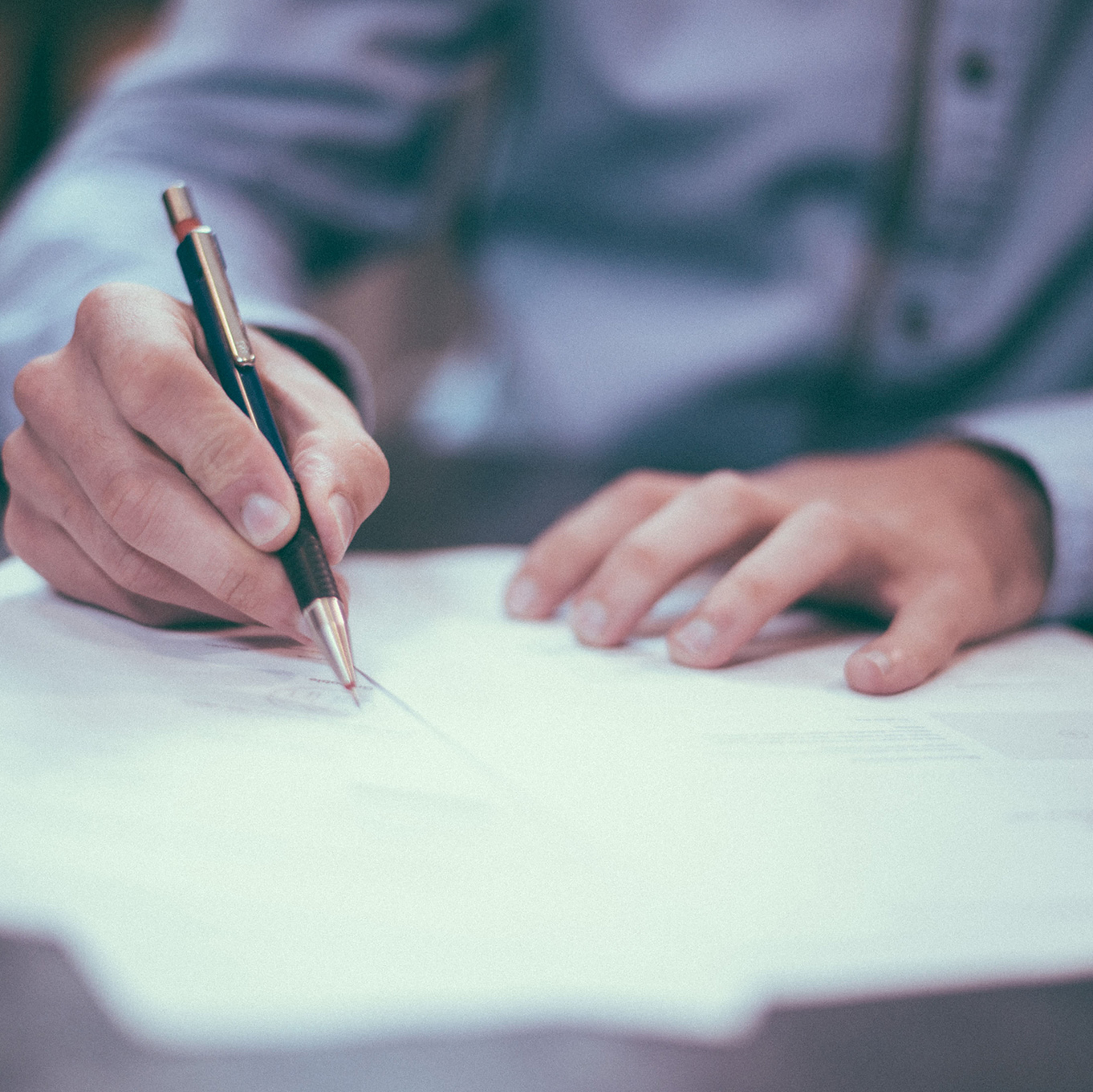 Smartly dressed person making notes on a document