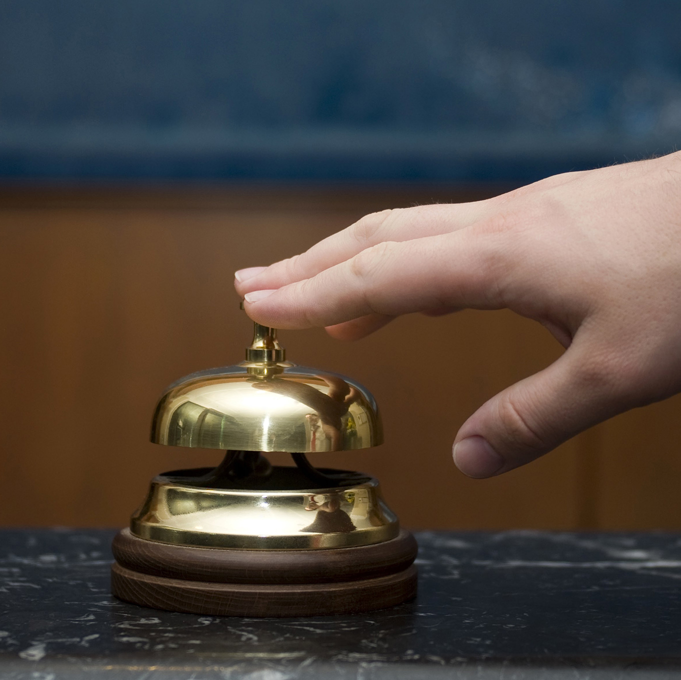 A hand reaches out to ring a service bell on a desk