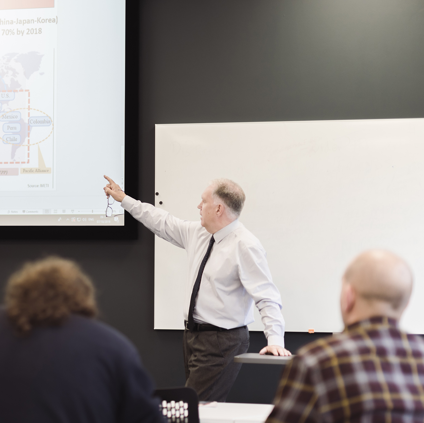 Students in a lecture - the lecturer is pointing at the projection of the presentation slides, while students take notes