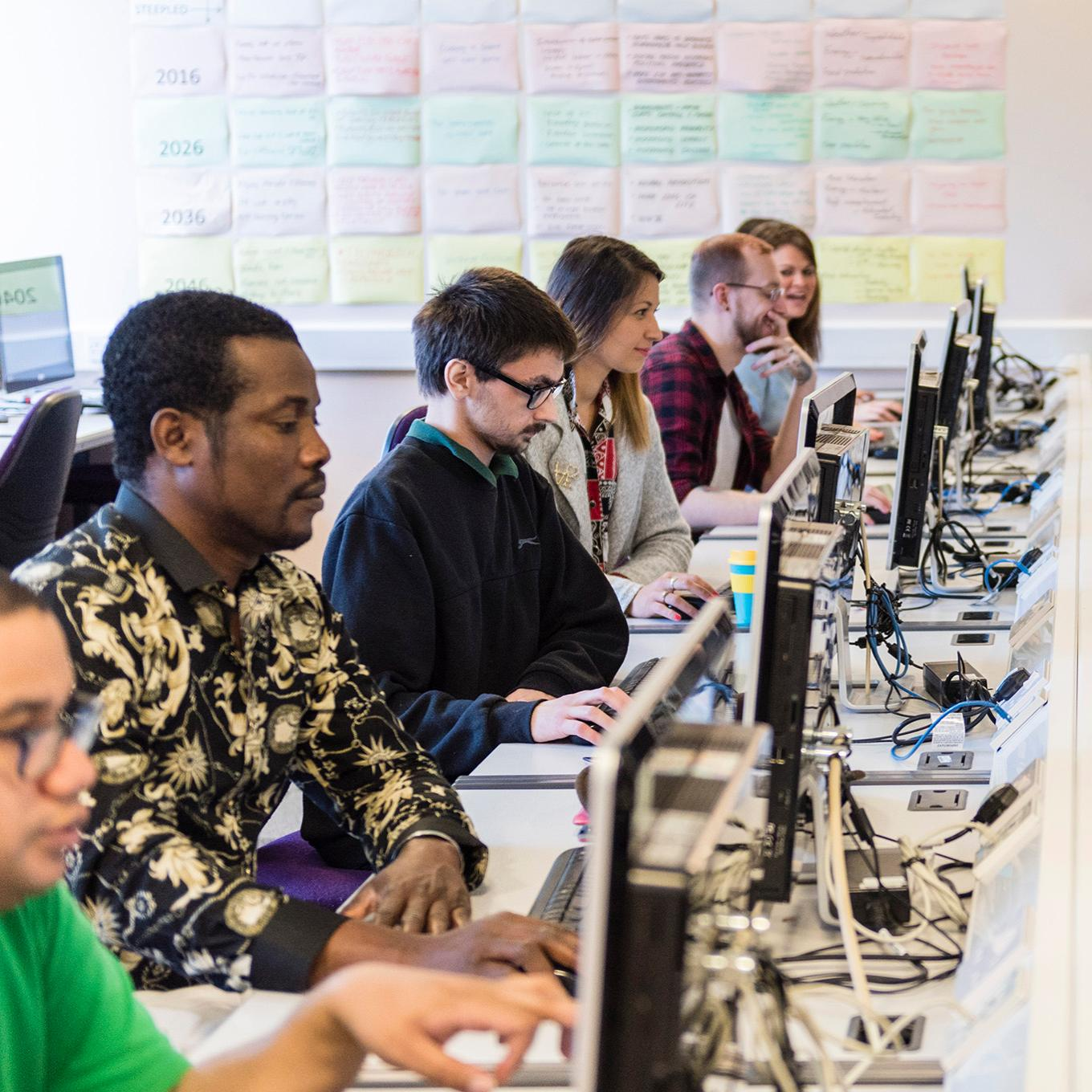 A row of computing students working in a computer lab