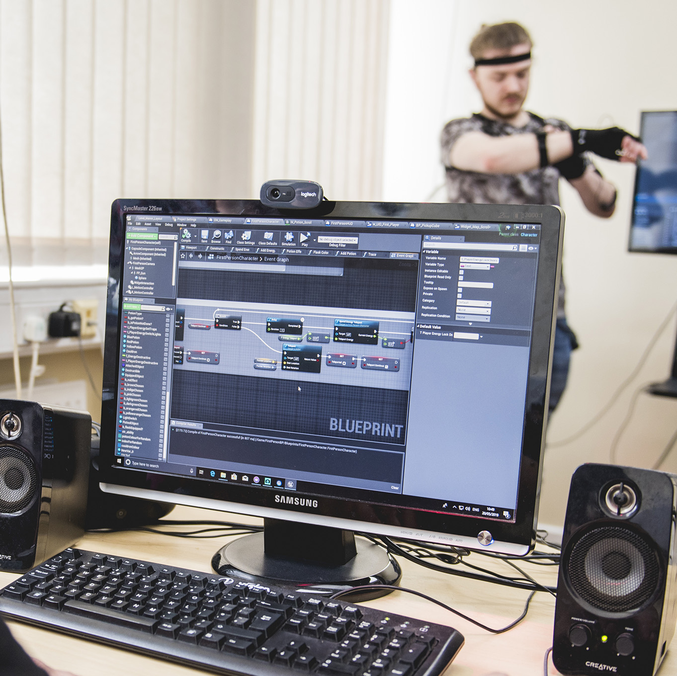 A computer monitor shows a project that a student is working on. In the backgroun, a student is wearing motion capture equipment.