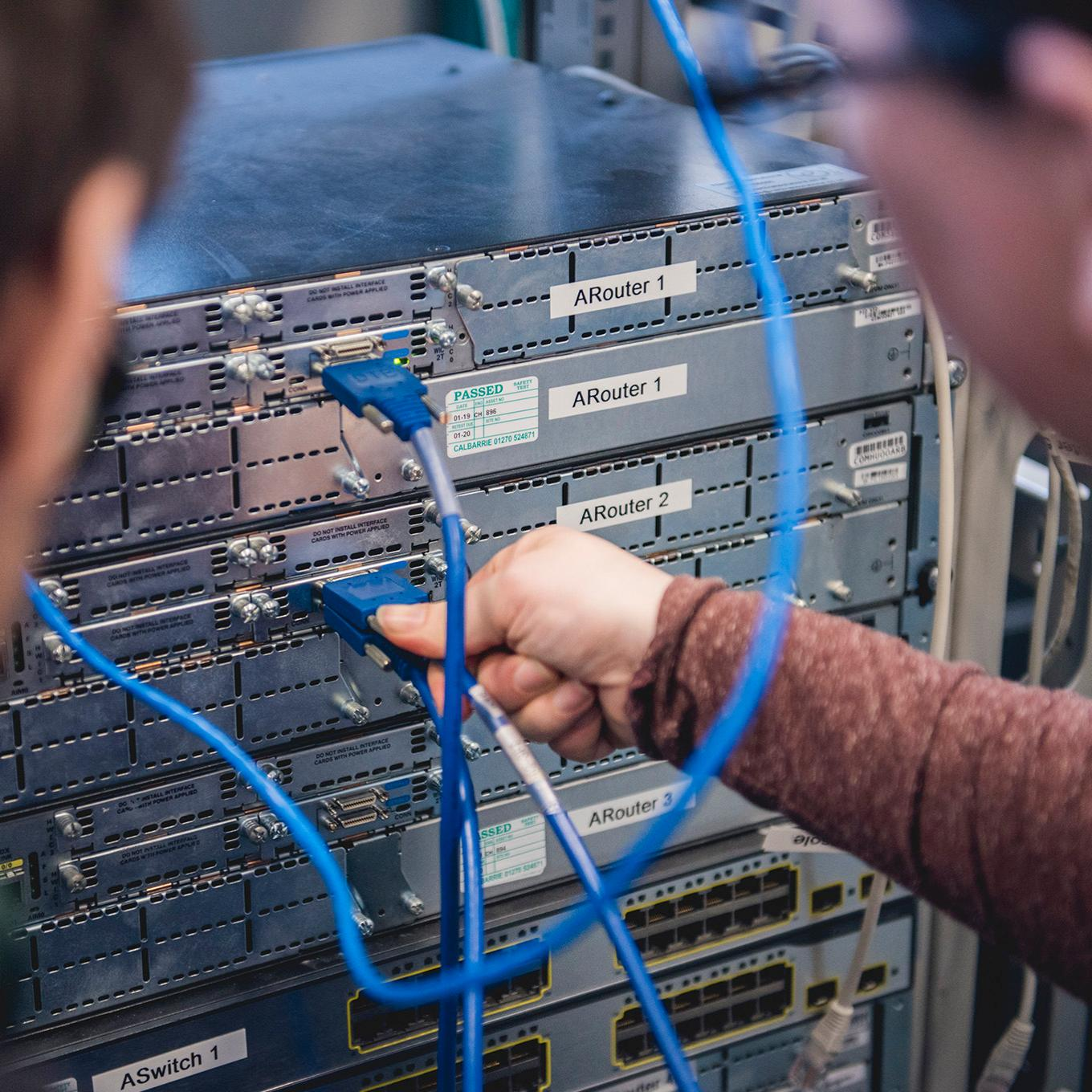 Two students face a server stack, one plugs in a cable