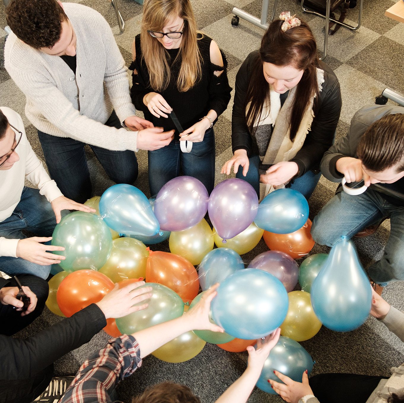 A group of students assemble balloons as part of a classroom task
