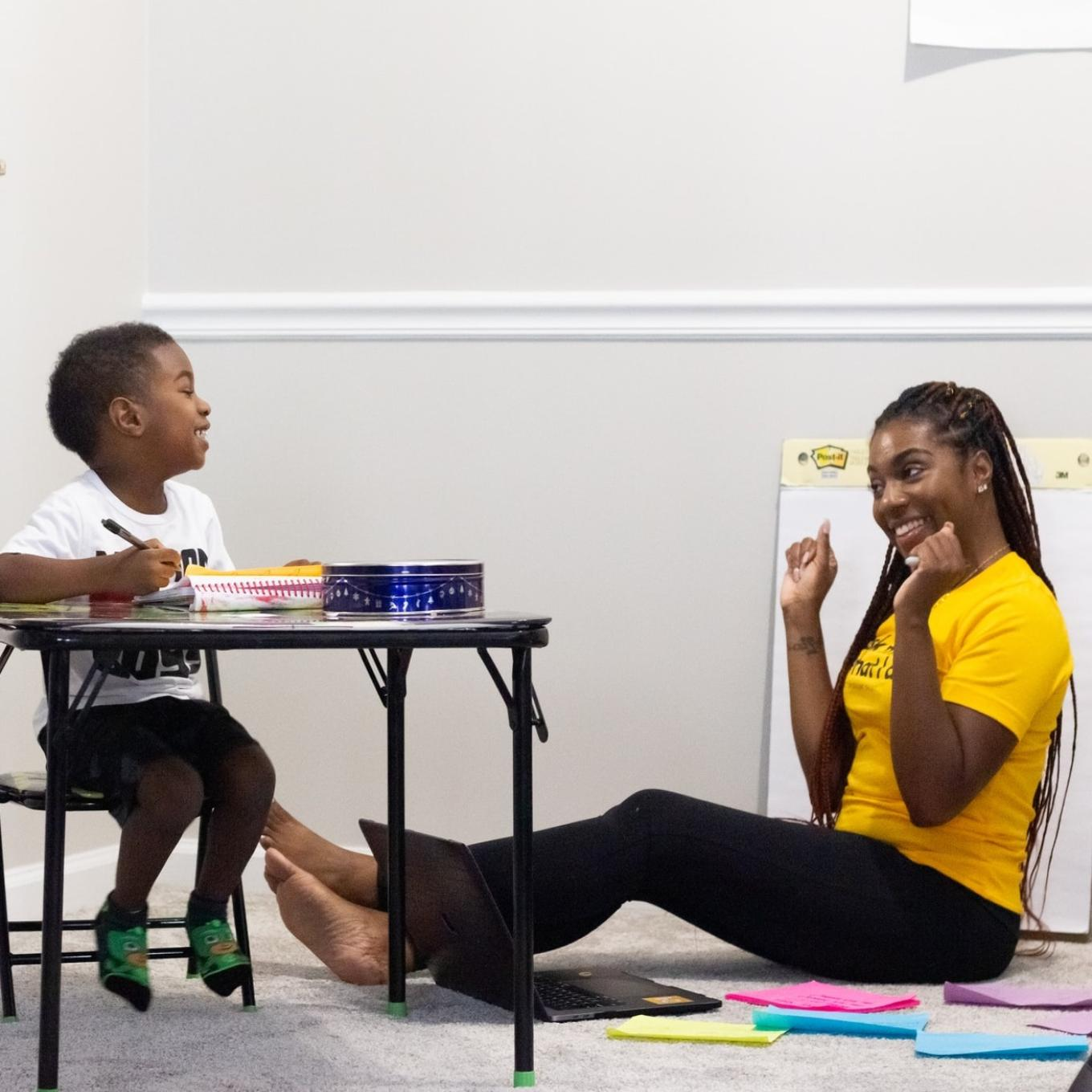 A woman sitting, laughing with a child sitting at a table