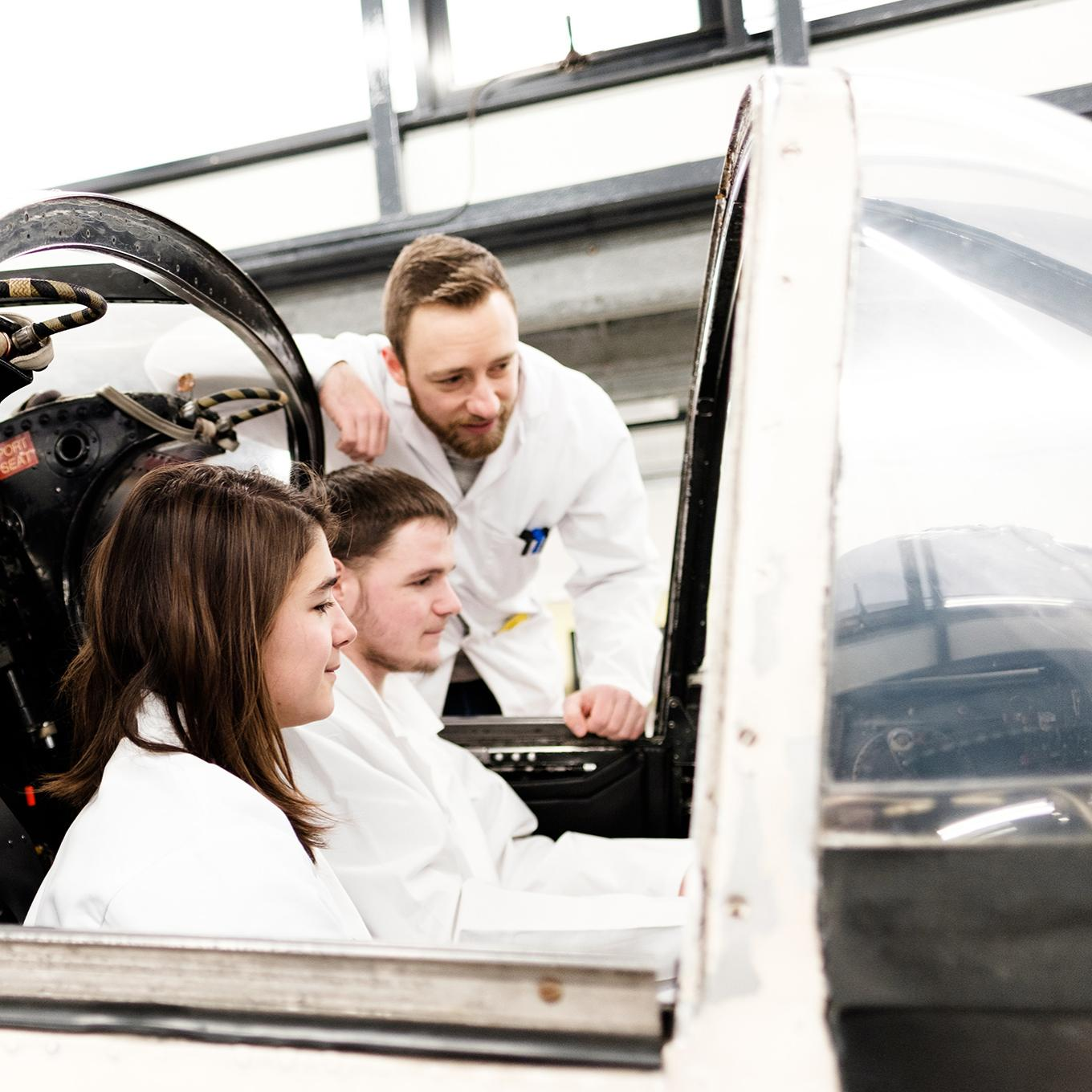 Two students sitting in the flight simulator, while another student leans in to look at the screens