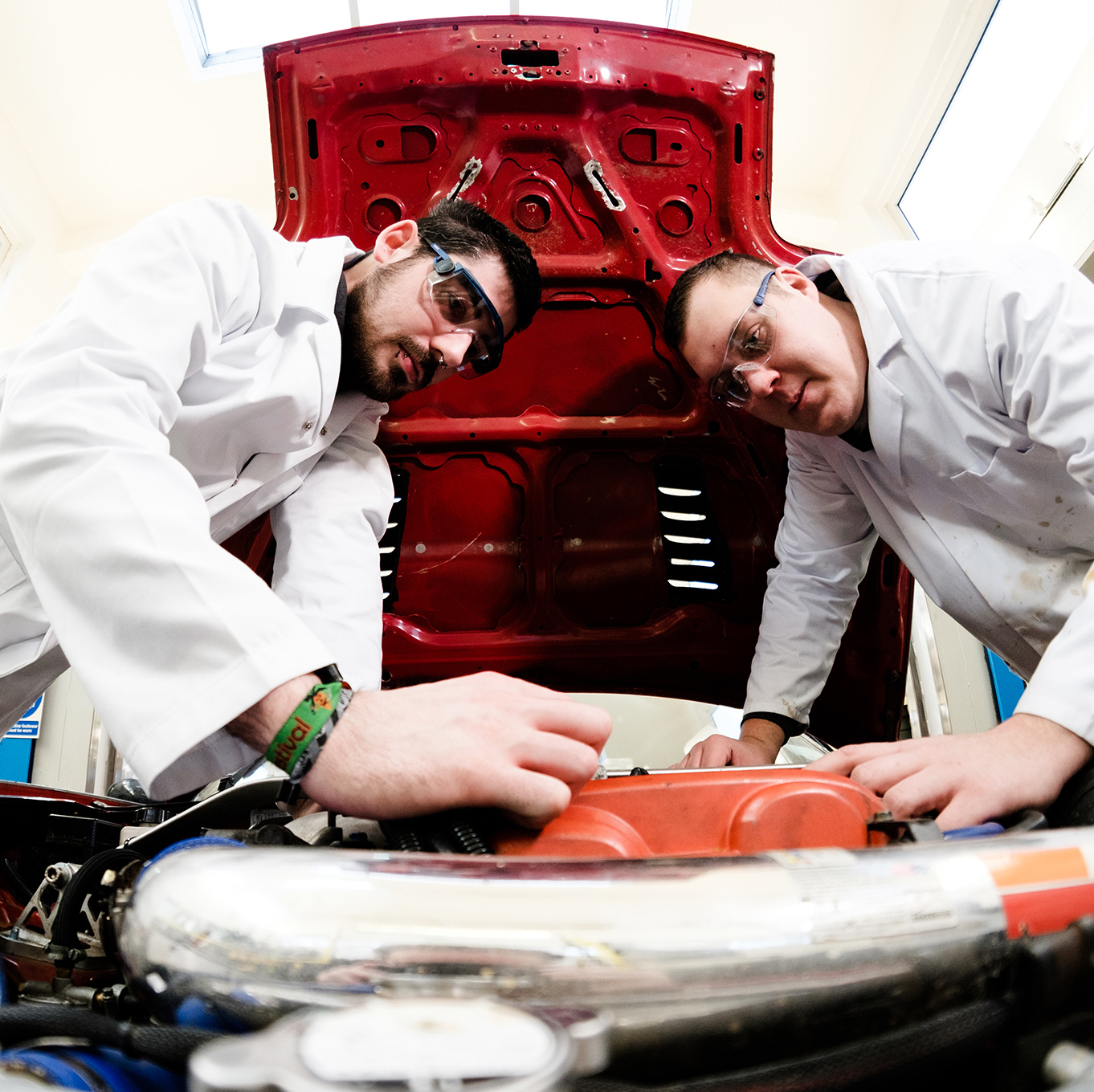 Two students wearing safety goggles working under the bonnet of a car