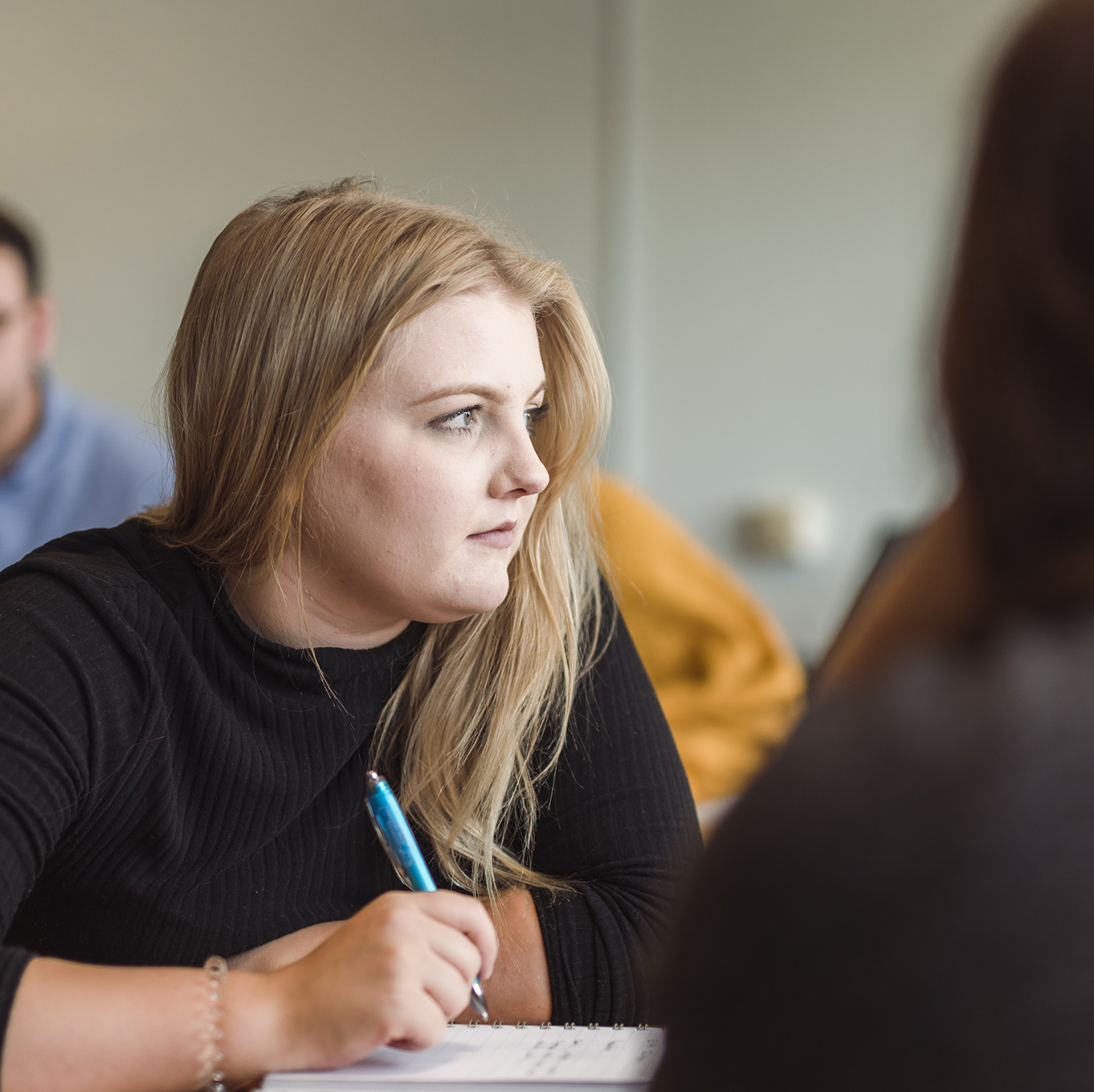 A student looks to the side, her pen poised over her notebook
