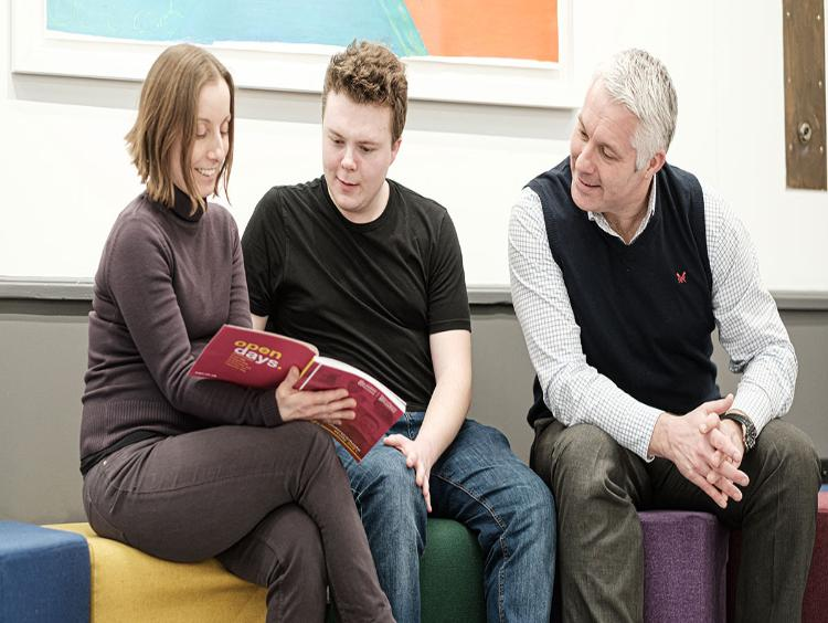 Parents looking at a prospectus with their son
