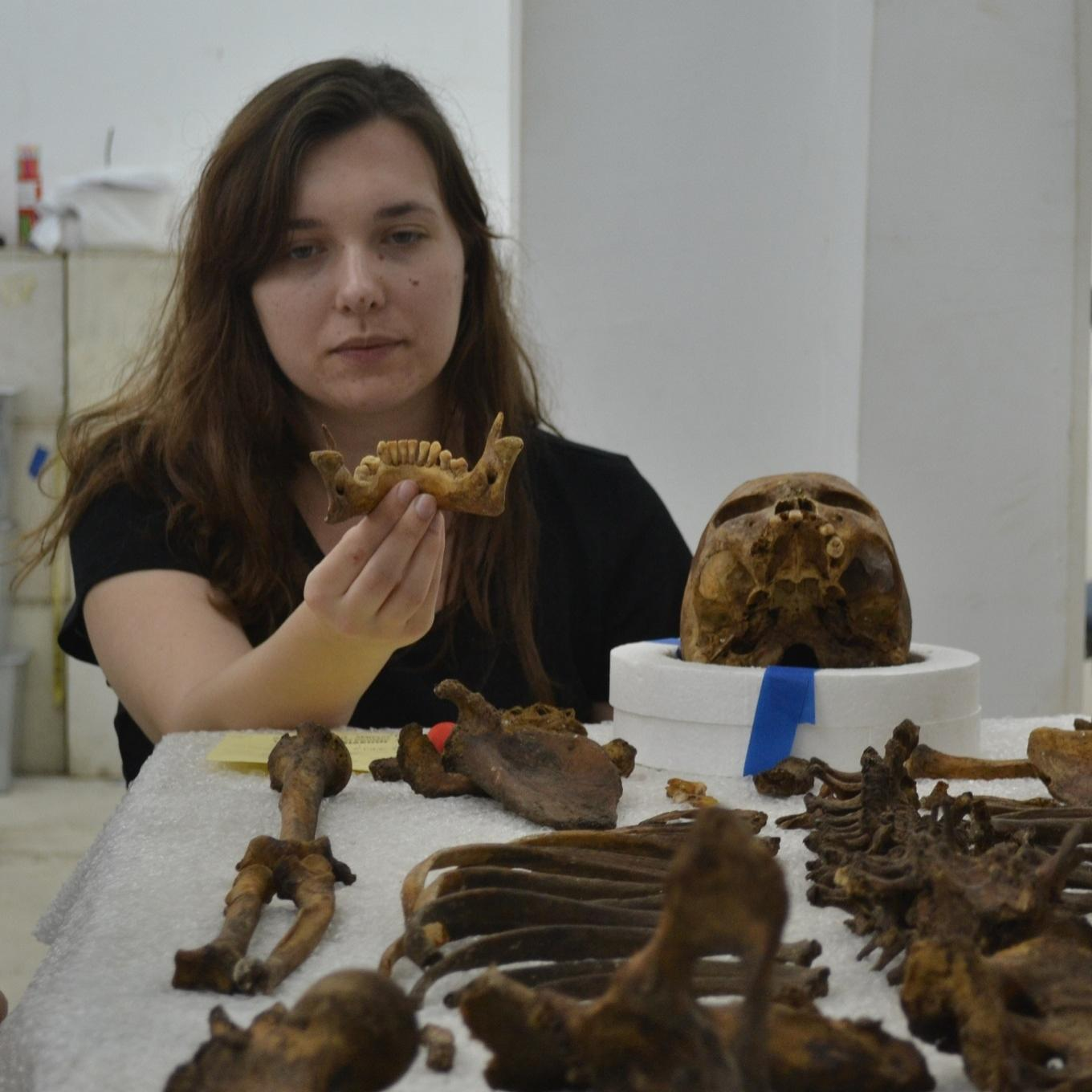 A forensics student examining a skeleton's remains