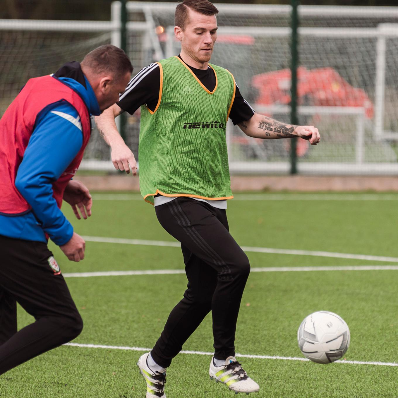 Two students playing football on the 3G pitch at Colliers Park training ground